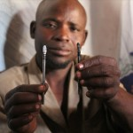 the 'wanzami' or village surgeon prepares the tools he uses for a boy's circumcision