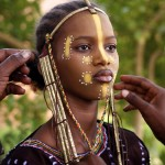 Teenage girl is dressed in traditional Fulani headgear and makeup by her father and uncle